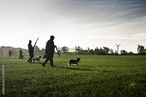 Foto op Canvas Jacht Hunter with hunting dog walks through field