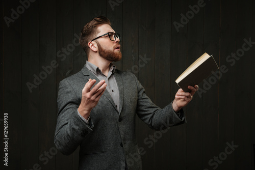 Valokuva  Man in eyeglasses reading book and gesturing with hands