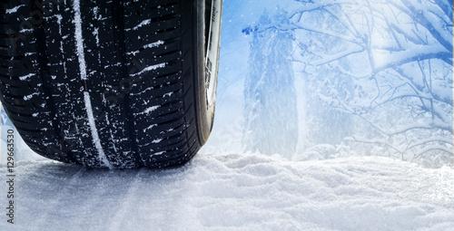 Zdjęcie XXL Samochodowe opony na śnieżnej drodze przed pogodnym śnieżnym lasem