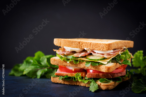 Poster Snack Big Club sandwich with ham, bacon, tomato, cucumber, cheese, eggs and herbs on dark background