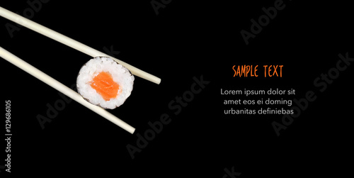 Chopsticks holding sushi isolated on black - Copyspace