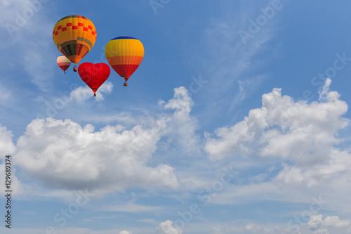 Plakat Balon na gorące powietrze wznosi się bardzo wysoko w błękitne niebo nad białymi chmurami
