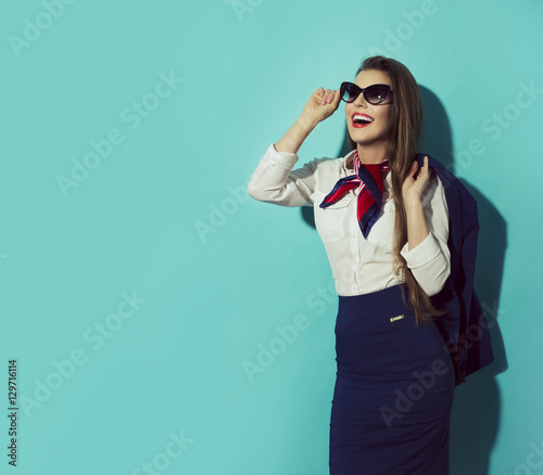 Happy stewardess with sunglasses on blue background looking left.