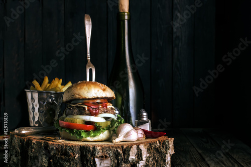 Fotografie, Obraz  Delicious burger with fries and garlic on dark rustic background