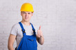 portrait of young handsome man in blue builder uniform thumbs up