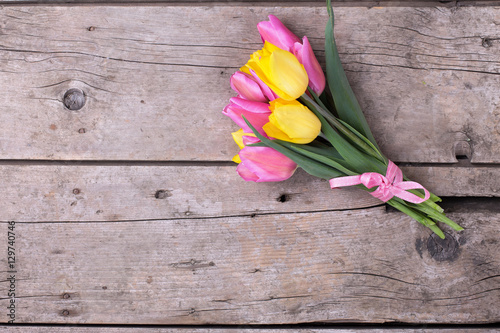 Photo  Bunch of bright yellow and pink spring tulips on wooden backgrou