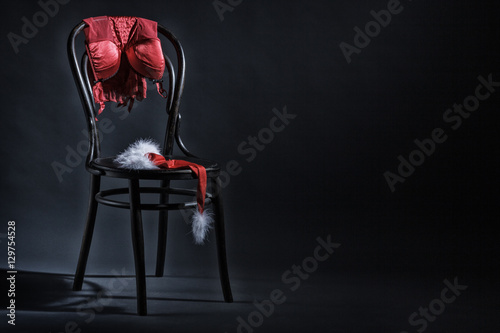 women-s-underwear-and-hat-of-santa-claus-hanging-on-a-retro-chair-erotic-christmas-motif