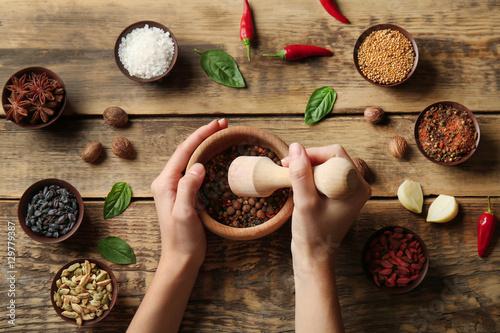 Keuken foto achterwand Kruiden Female hands grinding spices in mortar