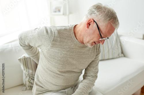 Fotografía  unhappy senior man suffering from backache at home