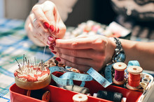 Woman Hands Trying To Thread A Needle Over The Box With Needlework Equipment