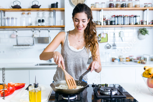 Fotografie, Obraz  Young woman frying onion into the pan in the kitchen.