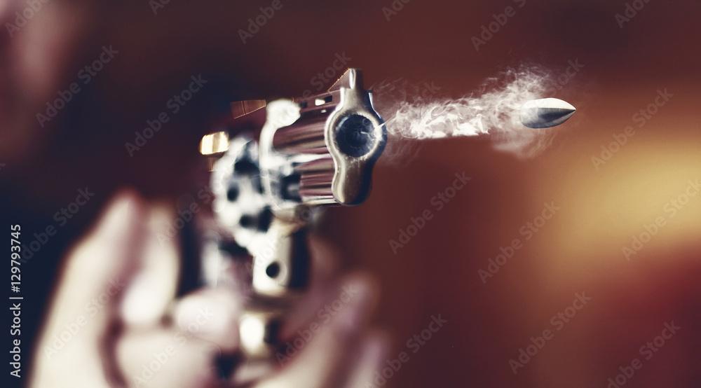 Fototapeta hand gun revolver with flying bullet fire