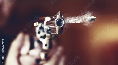 hand gun revolver with flying bullet fire Fototapeta