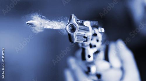 Fotografija hand gun revolver with flying bullet fire
