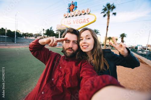 In de dag Las Vegas Happy young couple of tourists take selfie near Las Vegas Welcome sign. Two exited students take self portrait with a professional camera with Las Vegas billboard on the background, Nevada, USA
