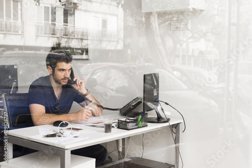Israel, Man sitting in office and talking on phone