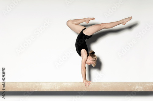 Side view of a young female doing a handstand on balance beam