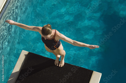 Photo High angle view of a female swimmer ready to dive while standing at the edge of