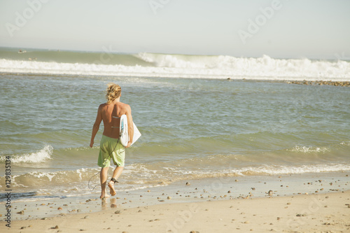 Plakat USA, California, Los Angeles, Venice, Man with surfing board walking on beach