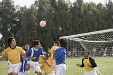 Group Of Players Playing Soccer On Field