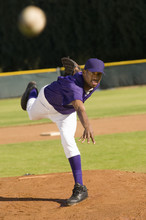 Young African American Baseball Pitcher Throwing The Ball