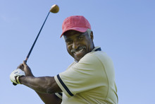 Portrait Of A Happy Senior Man Swinging A Golf Club Against Clear Sky