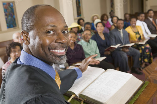 Fotografie, Obraz  Preacher at altar with Bible preaching to Congregation portrait close up