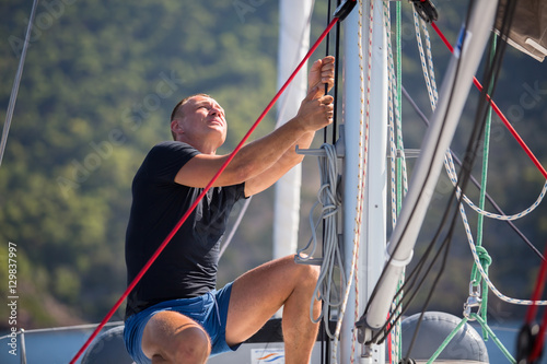Fotomural Yachtsman pulls the rope controlling the sail on sailing boat.
