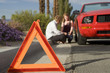 Emergency stop sign in foreground with blurred couple sitting by broken down car