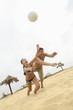 Tilt shot of a couple diving for volleyball on the beach