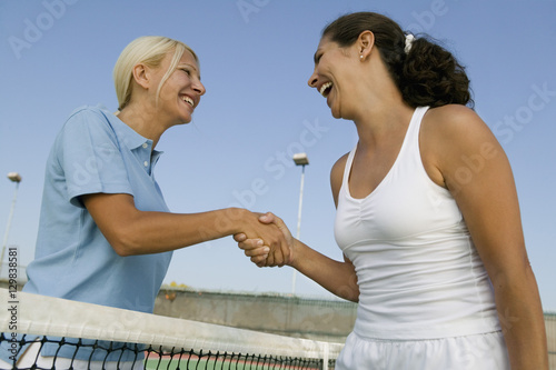 Fotografie, Obraz  Two female Tennis Players shaking hand over tennis court net low angle view