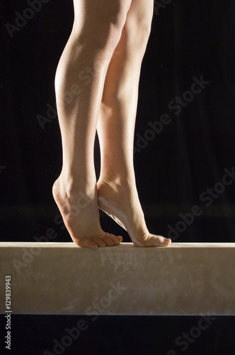 Spoed Fotobehang Gymnastiek Closeup low section of a female gymnast on balance beam against black background
