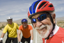 Close-up Of A Happy Senior Man With Friends Riding Bicycles In The Background
