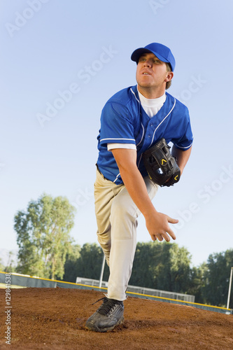 Photo  Baseball pitcher on pitcher's mound at full stretch after throwing a shot