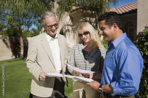 Poster Peche Happy couple with real estate agent discussing paperwork