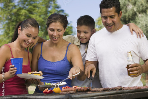 Photo  Boy with family gathered around the grill at picnic