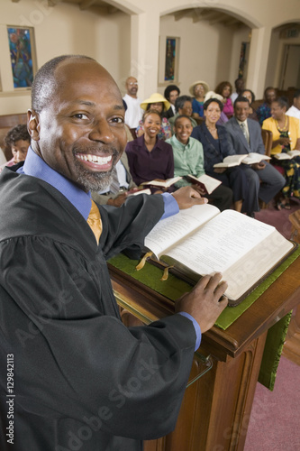 Preacher at altar with Bible preaching to Congregation portrait Canvas-taulu
