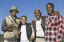 Portrait Of A Happy Multi Generation African Family Holding Fishing Rods