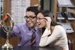 Happy Hispanic couple trying on glasses in the shop