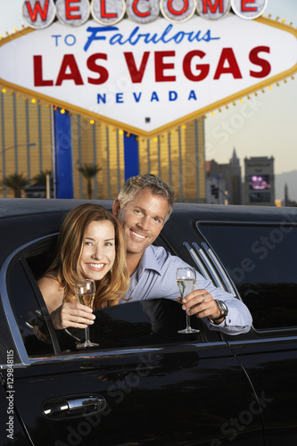 Photo  Happy couple in limousine with champagne flutes in front of welcome to Las Vegas