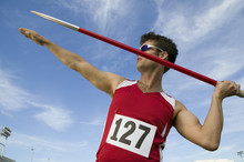 Young Male Athlete About To Throw Javelin Against The Sky