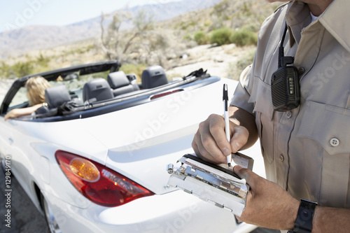 Fotografía  Closeup of a cropped police officer writing traffic ticket to woman sitting in c
