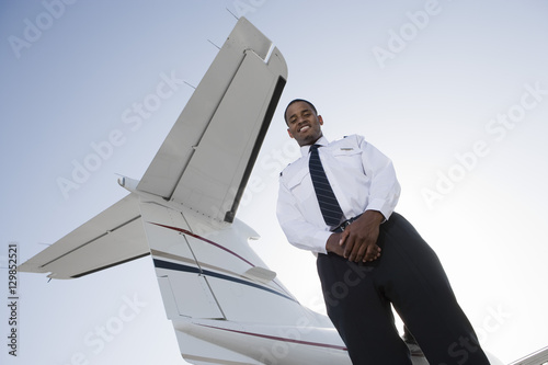 Photo  Low angle view of young pilot standing with airplane tail in background