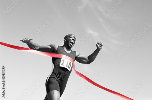 Obraz na plátně Low angle view of an African American male runner crossing finish line against b