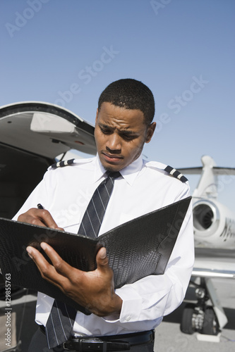 Photo  An airplane pilot taking notes on notepad with airplane in the background at air