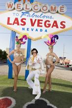 Portrait Of Elvis Presley Impersonator Standing With Casino Dancers Against Sign Board