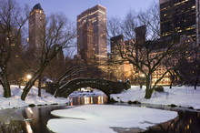 The Gapstow Bridge In Central Park After A Snowstorm With Skyscrapers Behind At Dusk, New York City, New York State, USA