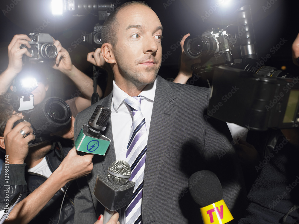 Fototapety, obrazy: Displeased man in suit surrounded by paparazzi