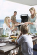 Family sitting around table eating barbecued food with father standing at grill grilling