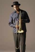 Serious African American Man With Trombone Standing Against Brown Background